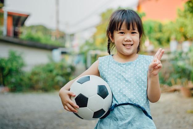 Portretten van kinderen spelen graag voetbal om te oefenen. Premium Foto