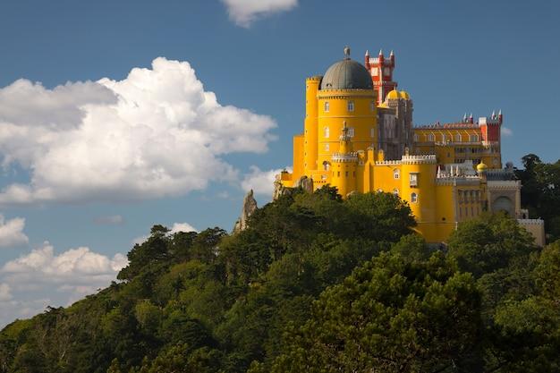 Portugal. sintra. het pena-paleis op een klif omgeven door bos en wolken Premium Foto