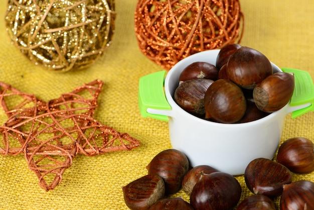 Portugese noten in keramische container over gele jute en met kerstversieringen Premium Foto