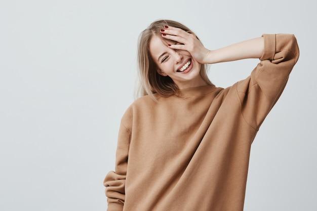 Positief aantrekkelijk blond jong model draagt een losse losse trui en is blij goed nieuws te ontvangen. blije vrouw verheugt zich in het weekend, binnenshuis ontspannen Gratis Foto