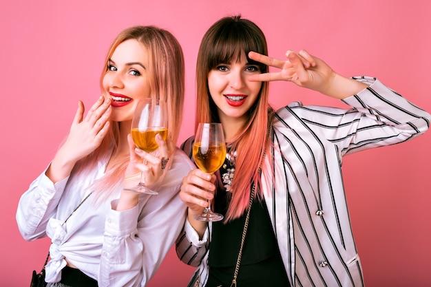 Positief binnenportret van twee stijlvolle elegante mooie vrouwen die plezier hebben op het feest, lekkere champagne drinken en dansen, cocktailavondoutfits en roze muur Gratis Foto