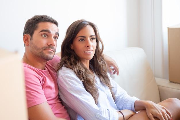 Positief gericht latijns paar zittend op de bank onder kartonnen dozen in nieuw appartement, wegkijken Gratis Foto