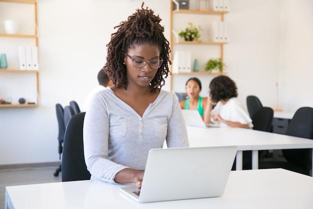 Positief gerichte afro-amerikaanse werknemer die op computer werkt Gratis Foto