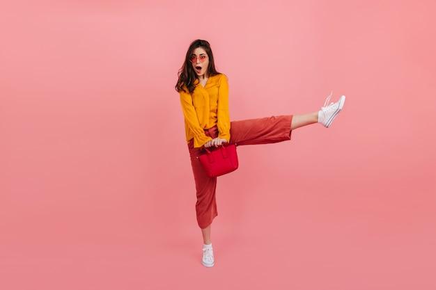 Positief meisje in modieuze lichte kleding stuitert hoog op roze muur. het portret van gemiddelde lengte van verraste brunette met rode zak. Gratis Foto
