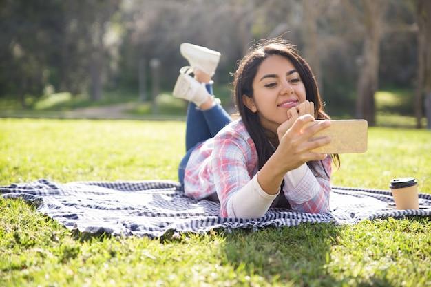 Positief mooi meisje dat van perfecte draadloze verbinding geniet Gratis Foto