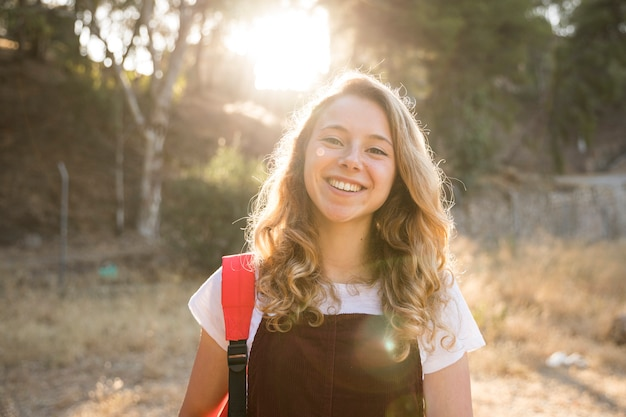 Positief tienermeisje dat in aard glimlacht Gratis Foto