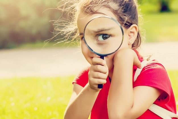 Positief vrolijk meisje dat door een vergrootglas in openlucht kijkt Premium Foto