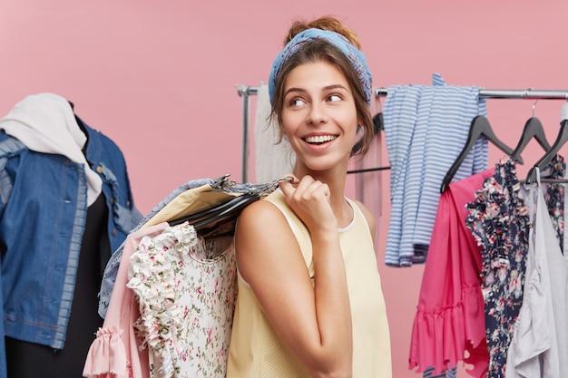 Positief wijfje dat zich zijdelings met hangers van kleren op schouders houdt, kijkend opzij wachtend op haar vriend die in paskamer is. vrouwelijk model is blij om boodschappen te doen en een nieuwe outfit te kopen Gratis Foto