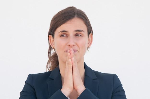 Positieve beambte die voor geluk bidt Gratis Foto
