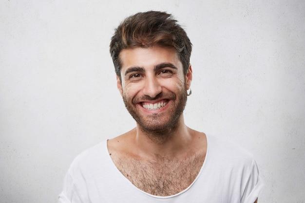 Positieve bebaarde man met donkere warme ogen met oorbel in het oor terloops gekleed met een aangename glimlach die zijn perfecte witte tanden toont met een goed humeur Gratis Foto