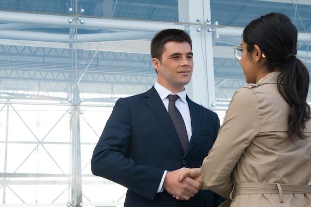 Positieve bedrijfsmensen die en handen in openlucht ontmoeten schudden Gratis Foto