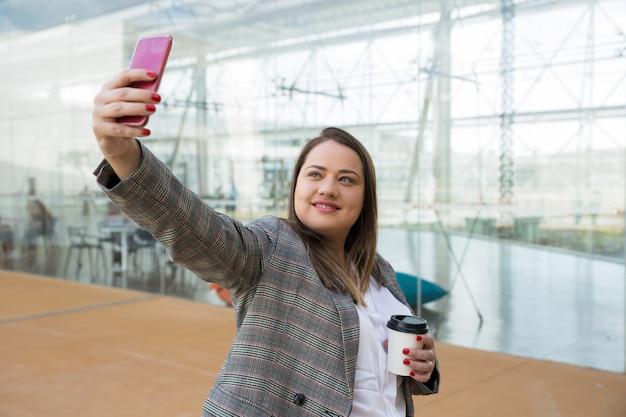 Positieve bedrijfsvrouw die selfie foto op telefoon in openlucht nemen Gratis Foto