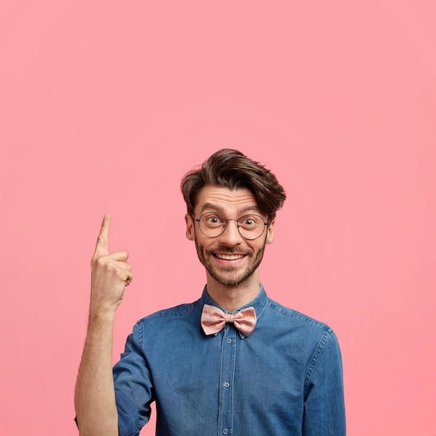 Positieve blanke man met trendy kapsel, donkere haren, blij iets hierboven op te merken, wijst met wijsvinger Gratis Foto