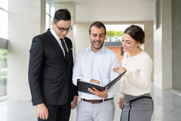 Positieve collega's die termen van bedrijfscontract bespreken Gratis Foto