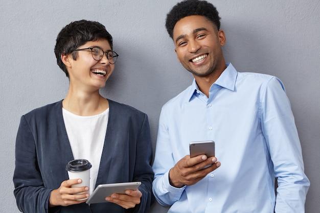Positieve collega's van gemengd ras werken met moderne tablets en smartphones Gratis Foto