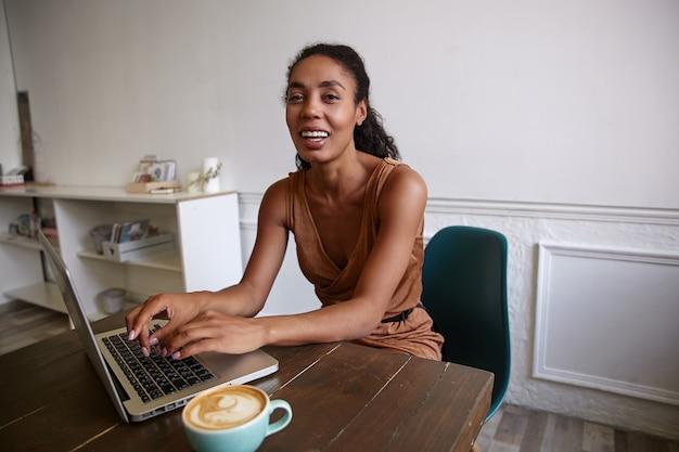 Positieve donkere vrouw met krullend haar die op afstand in koffiehuis werkt, haar handen op de sleutel houdt en vreugdevol kijkt Gratis Foto