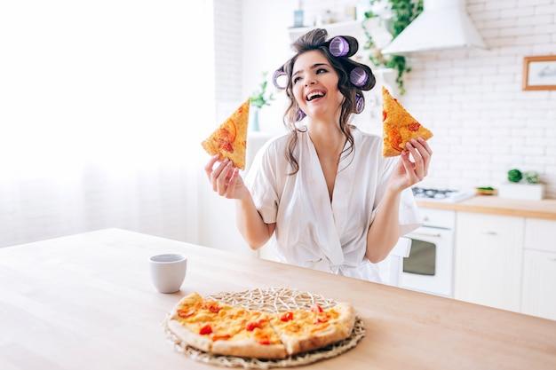 Positieve emotionele jonge zorgeloze huishoudster in keuken. houd twee plakjes pizza en glimlach. cup op tafel. alleen in de keuken. leven zonder werk. Premium Foto