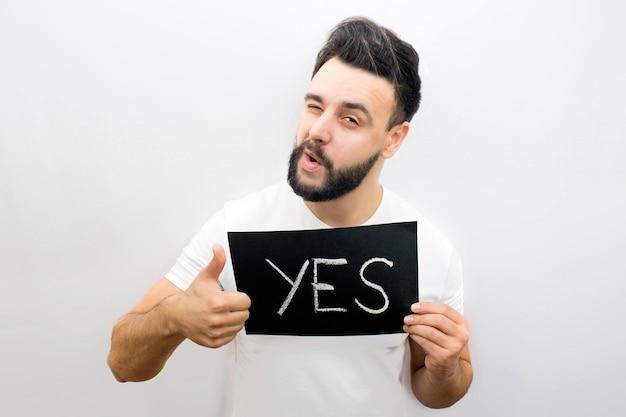 Positieve en speelse jongeman staan en kijkt. hij houdt een zwart bordje vast met het woord ja. ook toont de kerel zijn moerasduim omhoog en knipoogt met één oog. Premium Foto