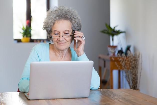 Positieve gepensioneerde dame die thuis werkt Gratis Foto