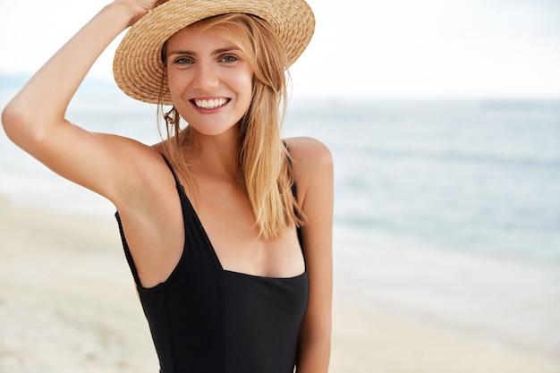 Positieve glimlachende ontspannen vrouw met een aantrekkelijk uiterlijk, draagt zwarte zwembroek, heeft een slank, perfect lichaam. Gratis Foto