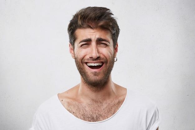 Positieve grappige bebaarde man met stijlvol kapsel zijn ogen sluiten terwijl hij oprecht glimlacht. vrolijke aantrekkelijke kerel met donkere baard die zijn gezicht van vreugde fronst Gratis Foto