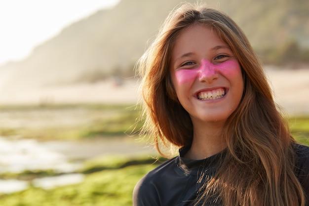 Positieve jonge blije europese vrouw met brede glimlach, heeft beschermend zinkmasker op gezicht dat zonnestralen blokkeert, draagt duikpak om te surfen, poseert buiten tegen de wazige kustlijnmuur. Gratis Foto