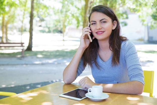 Positieve jonge dame die op telefoon bij koffielijst spreekt in park Gratis Foto