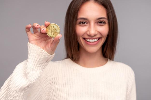 Positieve jonge vrouw bitcoin demonstreren Premium Foto