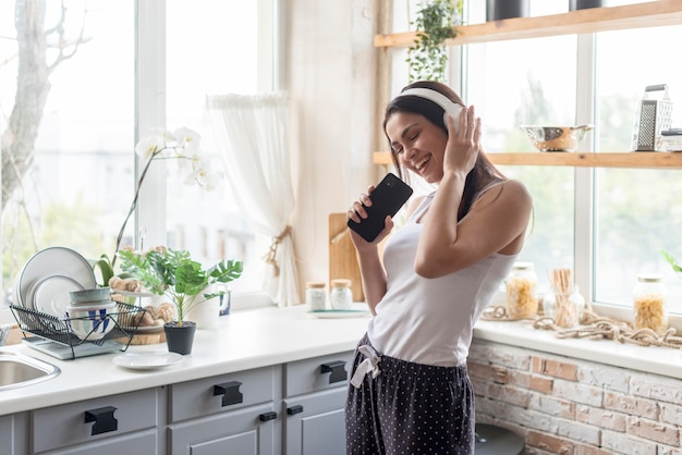 Positieve jonge vrouw die aan muziek luistert Premium Foto