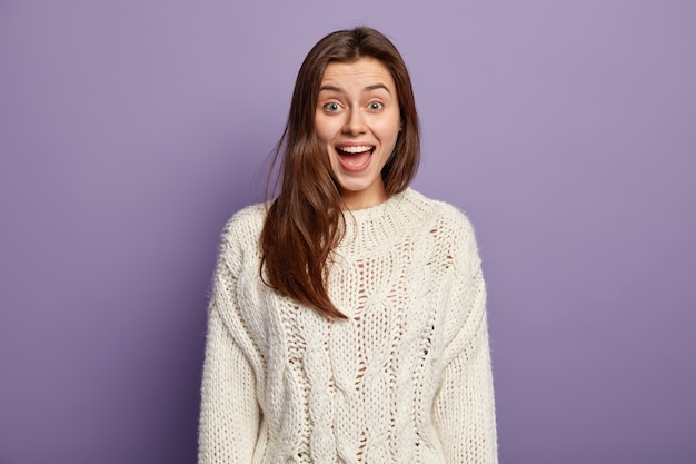 Positieve jonge vrouw met blije uitdrukking, opent mond van verbazing, reageert op positief onverwacht nieuws, draagt witte trui, staat tegen violette muur, geïntrigeerd door iets te vertellen Gratis Foto