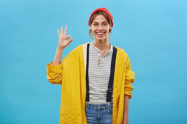 Positieve jonge vrouw terloops gekleed tonen ok teken met hand iets goed te keuren. vrouw in losse gele jas en rode hoed die over blauwe muur wordt geïsoleerd die met hand gebaart. vrolijk meisje werknemer Gratis Foto