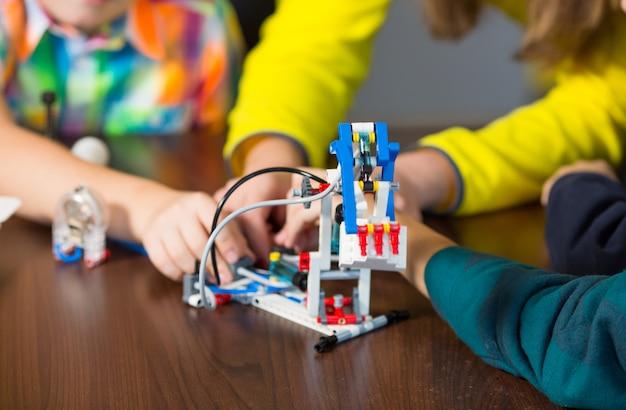 Positieve kinderen spelen en monteren de constructeur in de kinderkamer. Premium Foto