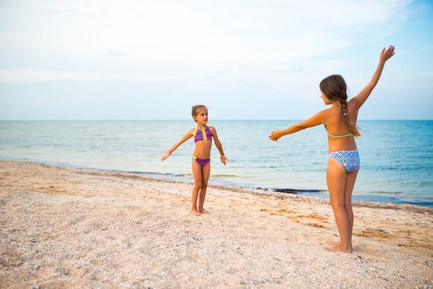 Positieve kleine meisjeszusjes spelen actieve spelletjes op het zandstrand tijdens de zomervakantie op een zonnige warme zomerdag Premium Foto