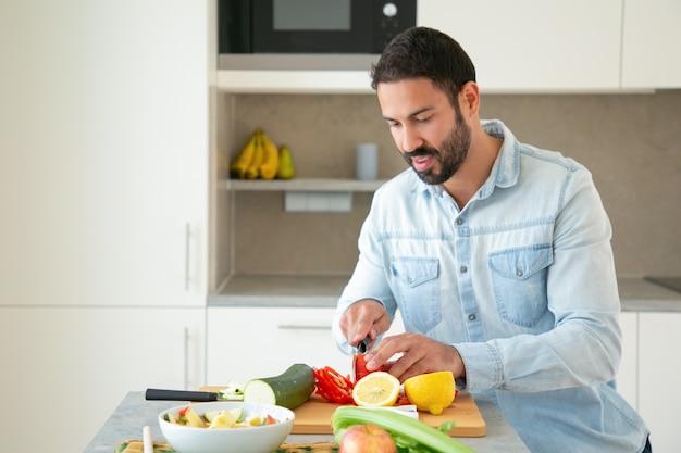 Positieve knappe man koken salade, verse groenten snijden op snijplank in de keuken. medium shot, kopie ruimte. gezond voedselconcept Gratis Foto