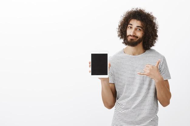 Positieve knappe mannelijke chirurg in gestreept t-shirt, met witte digitale tablet en stedelijke gebaar maken Gratis Foto