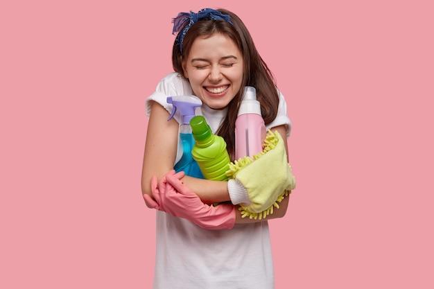 Positieve lachende donkerharige vrouw omarmt flessen wasmiddelen en reinigingssprays, deodorant Gratis Foto