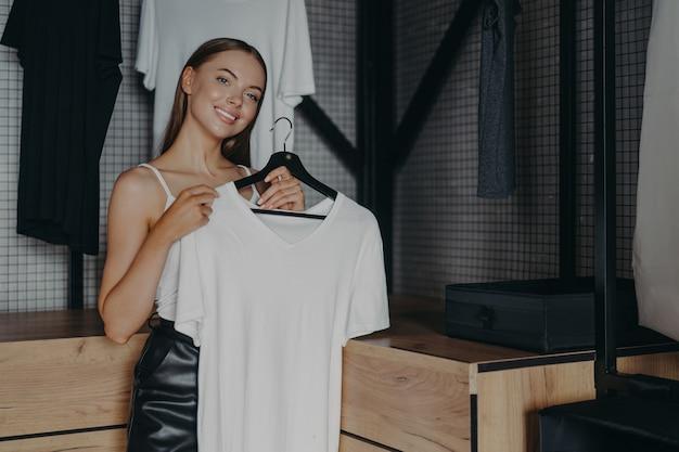 Positieve lachende vrouw jurken voor speciale gelegenheid houdt witte jurk op hangers vormt over huis garderobe Premium Foto