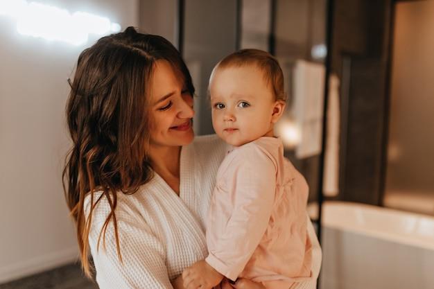 Positieve langharige vrouw in wit gewaad met tedere glimlach kijkt naar haar dochtertje. Gratis Foto