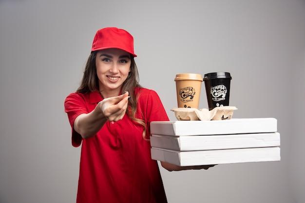 Positieve levering vrouw met pizza en koffiekoppen op grijze muur. Gratis Foto