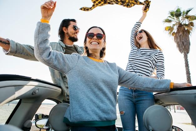 Positieve man en glimlachende vrouwen met plezier en leunend uit de auto Gratis Foto