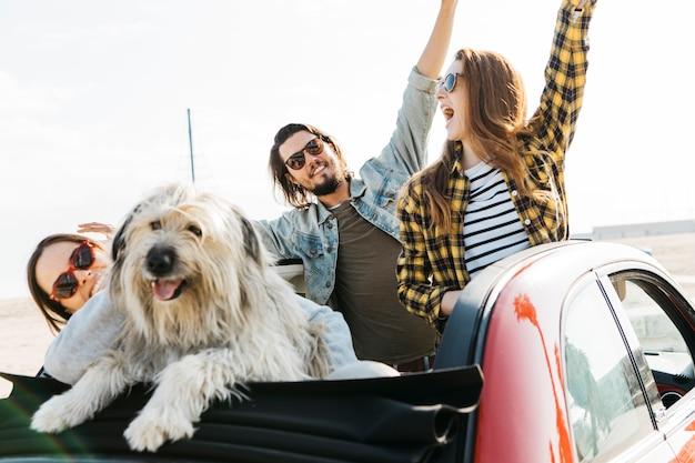Positieve man en glimlachende vrouwen met upped handen dichtbij hond die uit auto leunt Gratis Foto