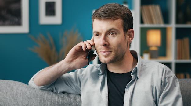 Positieve man in vrijetijdskleding praten over mobiel zittend op de bank in appartement, shot van de borst Premium Foto