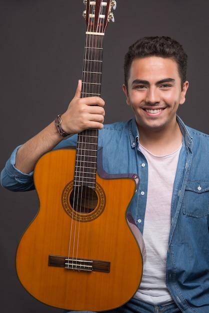 Positieve man met een mooie gitaar op zwarte achtergrond. hoge kwaliteit foto Gratis Foto