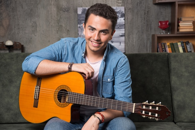 Positieve man zittend op de bank met een mooie gitaar. hoge kwaliteit foto Gratis Foto