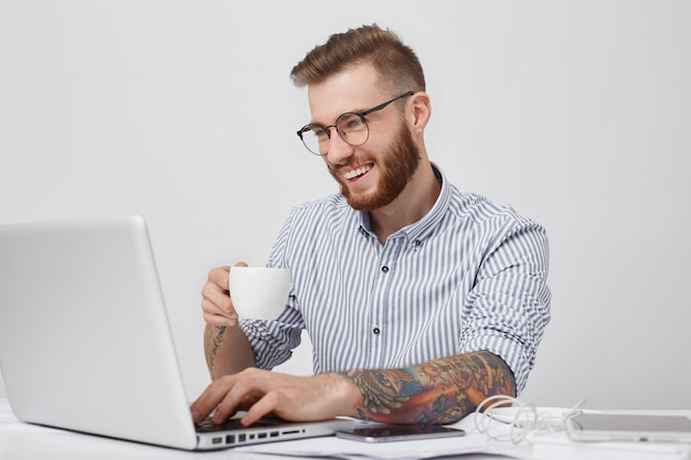 Positieve mannelijke studentenberichten op sociale netwerken met vrienden, hebben een aangename glimlach Gratis Foto