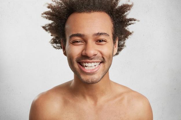 Positieve menselijke emoties concept. knappe jongeman lacht graag, toont perfecte witte tanden Gratis Foto