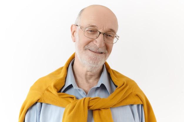 Positieve menselijke emoties, gevoelens en houding. foto van gelukkige aantrekkelijke gepensioneerde man met witte baard en kale kop vreugde en plezier uitdrukken, camera kijken met vrolijke vriendelijke glimlach Gratis Foto