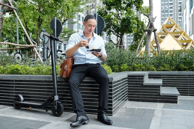 Positieve mixed-race ondernemer zittend op borstwering en met heerlijk straatvoedsel voor de lunch Premium Foto