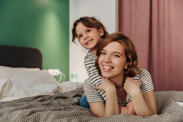 Positieve moeder en dochter met plezier, knuffelen en liggend op bed. Gratis Foto