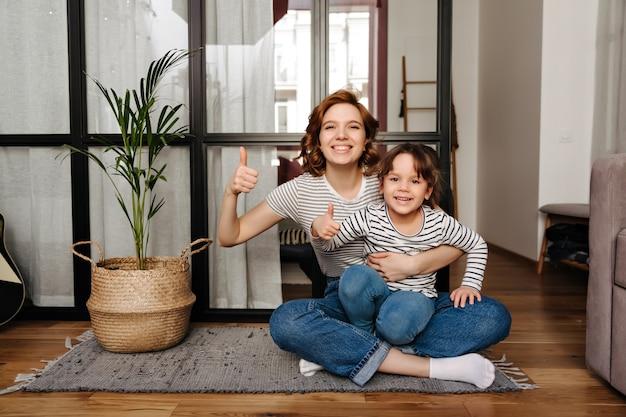 Positieve moeder en haar kleine ondeugende dochter zitten op een tapijt en laten hun duimen zien. Gratis Foto